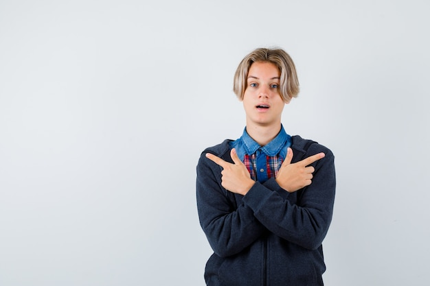 Bonito rapaz adolescente com camisa, moletom apontando para a esquerda e direita e parecendo indeciso, vista frontal.