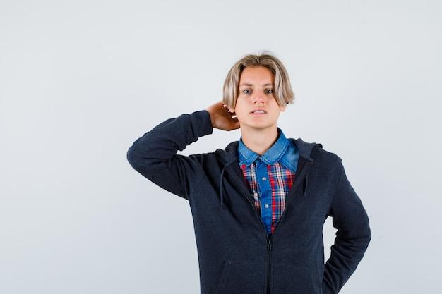 Bonito rapaz adolescente com camisa, moletom com a mão atrás da cabeça e olhando pensativo, vista frontal.