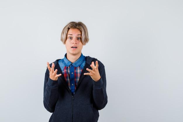 Bonito rapaz adolescente com camisa, moletom com capuz, levantando as mãos em um gesto de questionamento e parecendo perplexo, vista frontal.