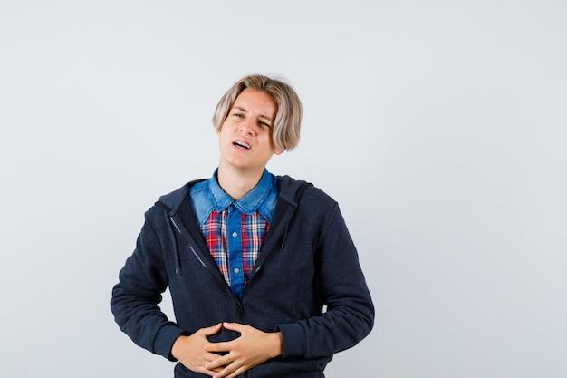 Bonito rapaz adolescente com camisa, moletom com capuz, sofrendo de dor de estômago e parecendo incomodado, vista frontal.