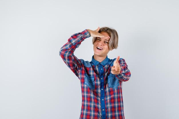 Bonito rapaz adolescente com camisa quadrada, apontando para a frente, com a mão na cabeça e olhando enérgico, vista frontal.