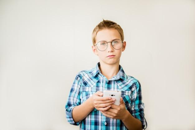 Bonito rapaz adolescente de óculos com telefone