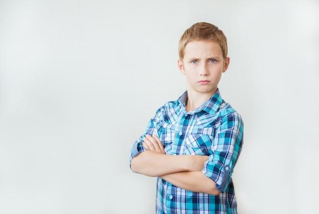 Bonito rapaz adolescente em pé com os braços cruzados