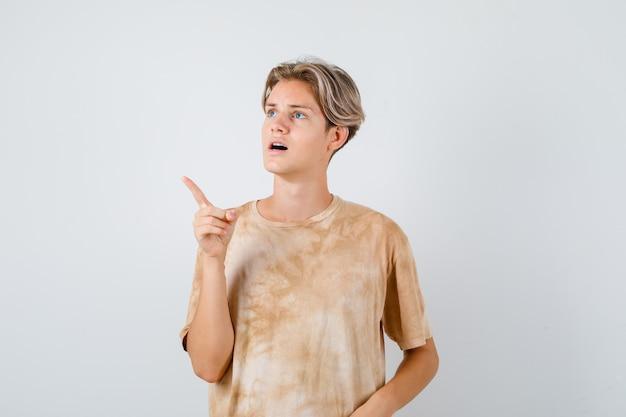Bonito rapaz adolescente em t-shirt apontando para o canto superior esquerdo, olhando para longe e parecendo perplexo, vista frontal.