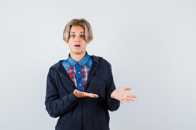 Bonito rapaz adolescente fingindo mostrar algo na camisa, moletom com capuz e parecendo perplexo. vista frontal.