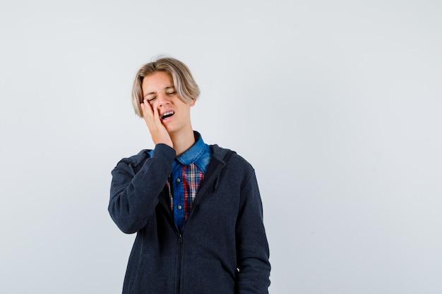 Bonito rapaz adolescente mantendo a mão na bochecha na camisa, moletom com capuz e parecendo esquecido. vista frontal.