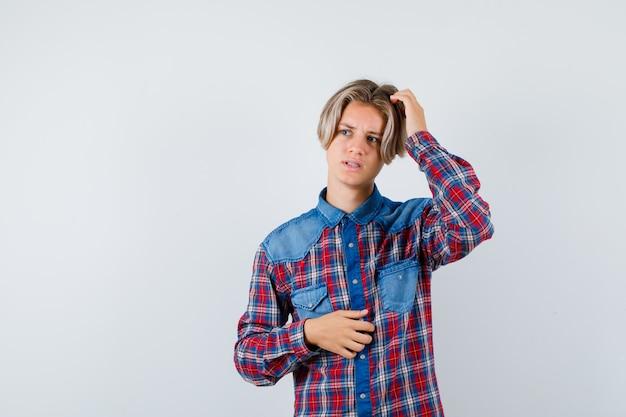 Bonito rapaz adolescente numa camisa quadriculada, coçando a cabeça, desviando o olhar e parecendo preocupado, vista frontal.