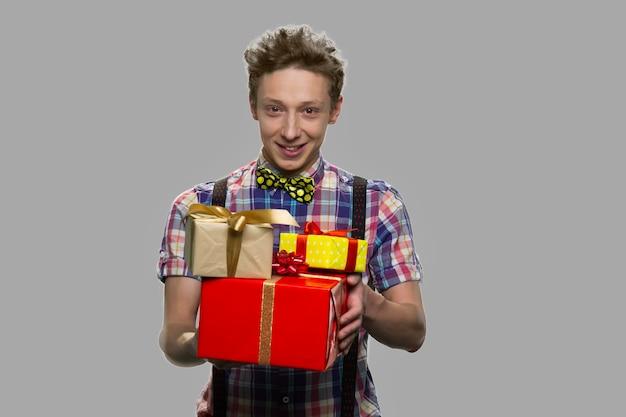 Bonito rapaz adolescente segurando caixas de presente. cara adolescente bonito oferecendo caixas de presentes contra um fundo cinza.
