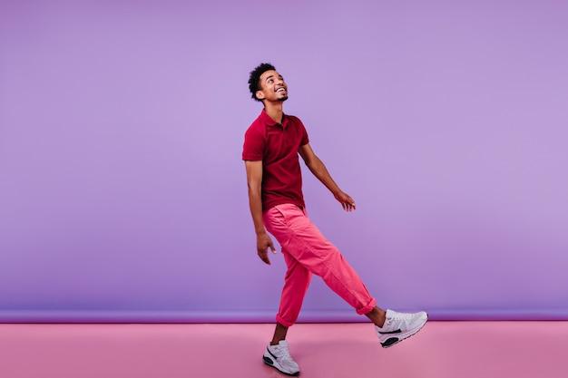 Bonito rapaz africano em calças da moda, olhando para cima com um sorriso. foto interna do modelo masculino negro interessado dançando.