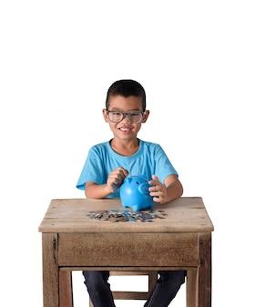 Bonito rapaz asiático colocando moedas no cofrinho isolado no fundo branco