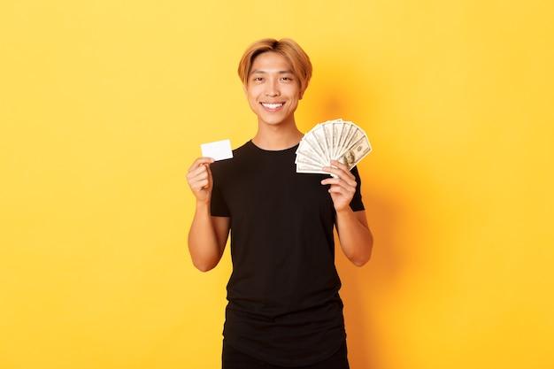 Bonito rapaz asiático satisfeito mostrando dinheiro e cartão de crédito, sorrindo, feliz, parado na parede amarela
