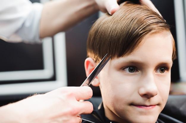 Bonito rapaz cortando o cabelo em um salão de beleza