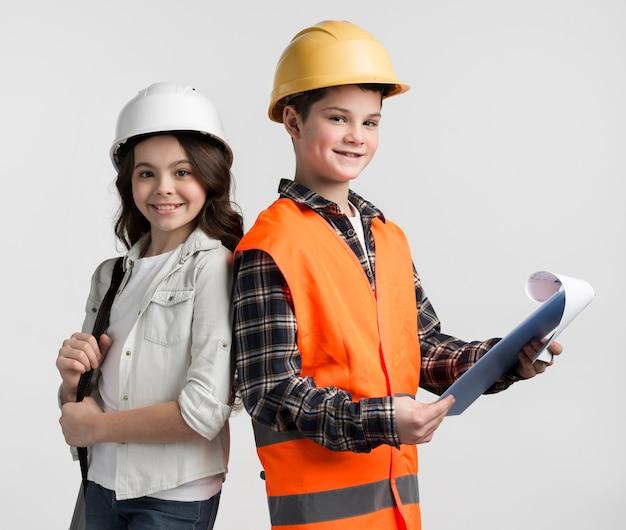Bonito rapaz e rapariga posando como engenheiros