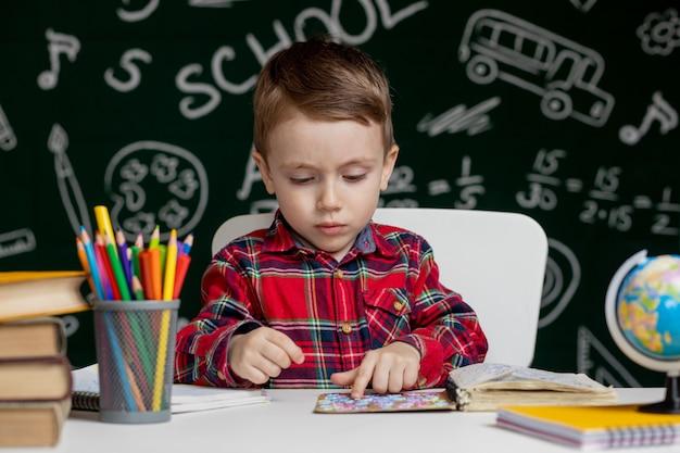 Bonito rapaz inteligente está sentado em uma mesa com lupa na mão. criança está lendo um livro com um quadro negro sobre fundo. pronto para a escola. de volta à escola