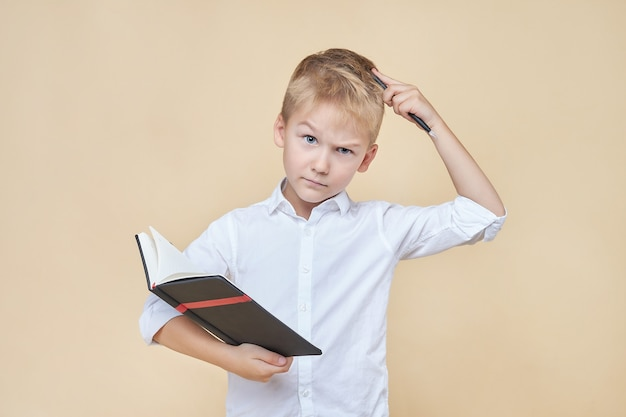 Bonito rapaz inteligente pensativo e coça a cabeça com uma caneta enquanto segura um caderno nas mãos.