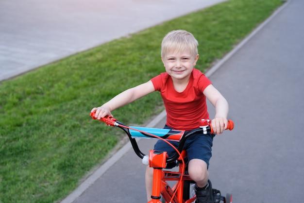 Bonito rapaz loiro passeios de bicicleta infantil