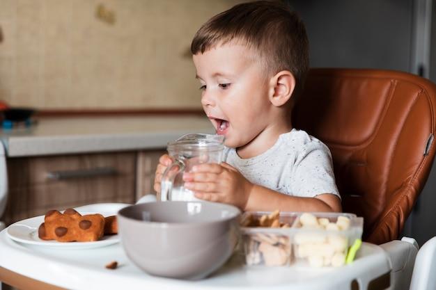 Bonito rapaz segurando o frasco de leite