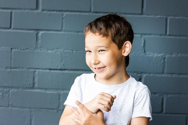 Bonito rapaz sorridente de 8 anos de idade confuso sobre o fundo da parede de tijolo cinza