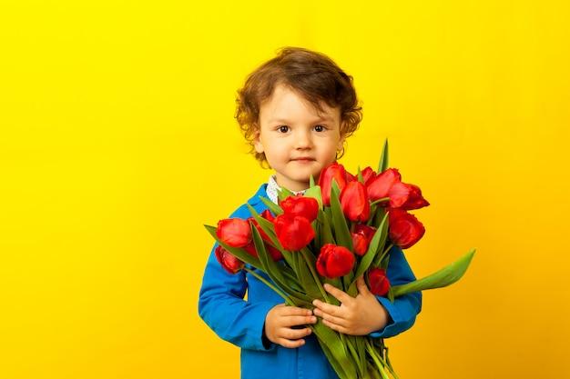 Bonito rapaz sorridente encaracolado com um buquê de tulipas vermelhas para a mãe. dia das mães.