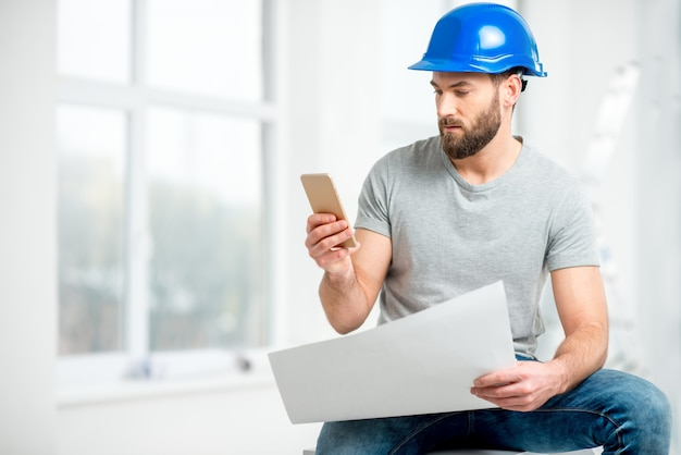 Bonito reparador ou construtor de capacete trabalhando com desenhos e telefone na renovação do interior do apartamento
