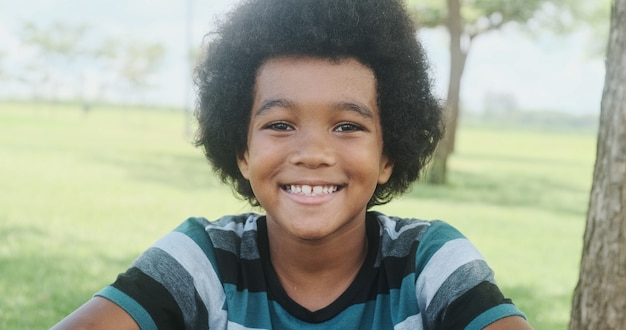 Bonito retrato ao ar livre de um sorridente jovem afro-americano.