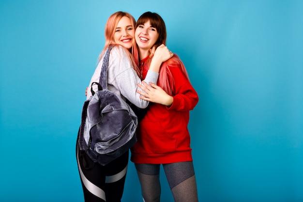 Bonito retrato brilhante de duas meninas felizes bonitas hippie vestindo roupas esportivas para fitness e mochila, sorrindo e abraços, parede azul.