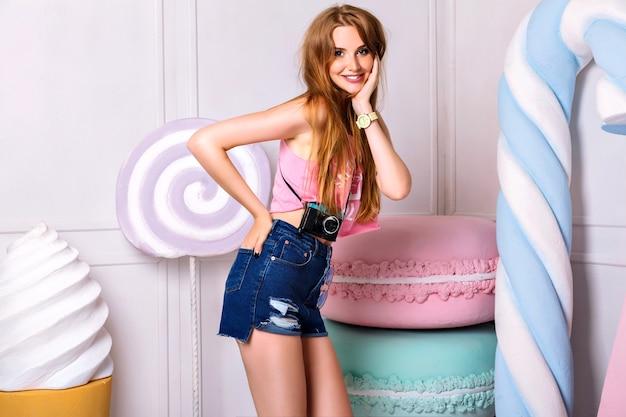 Bonito retrato interior de uma jovem mulher bonita perto de enormes doces coloridos adereços. sorrindo, segurando a mão perto do rosto. menina vestindo camiseta rosa de verão e short azul
