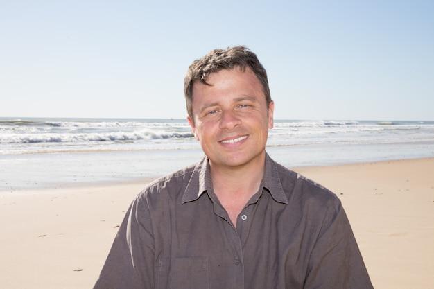 Bonito rosto sorridente de homem com fundo de praia do mar de areia