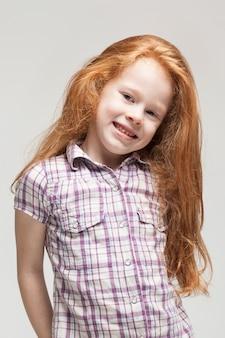 Bonito ruiva menina na camisa xadrez, calças azuis brilhantes e botas brancas