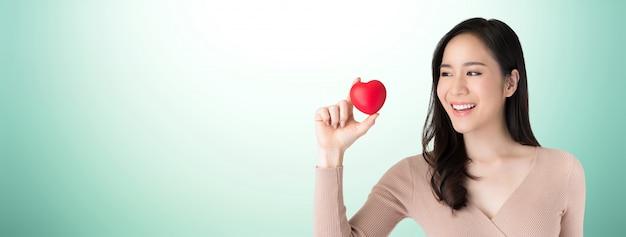 Bonito, saudável, jovem, mulher asian, segurando, e, olhar, coração vermelho, bola