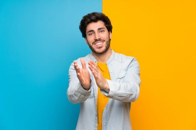 Bonito sobre parede colorida isolada aplaudindo após apresentação em uma conferência