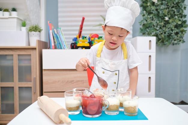 Bonito sorridente asiático menino de 4 anos de idade com um rolo se divertindo cozinhar bolo de morango em casa, diversão atividades internas para o conceito de jardim de infância