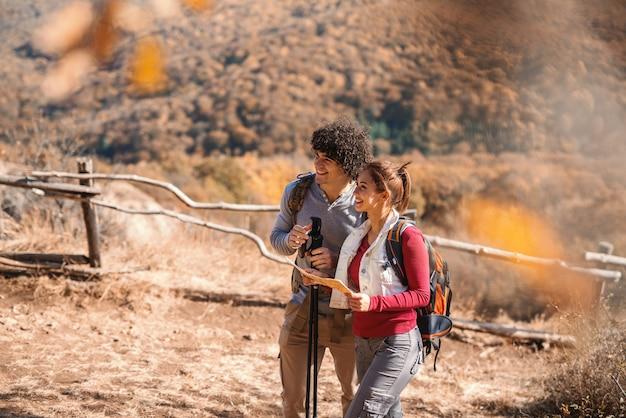 Bonito sorridente casal caucasiano caminhadas. mulher segurando o mapa, nas mochilas de costas.