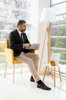 Bonito sorridente empresário maduro com tablet no escritório trabalhando