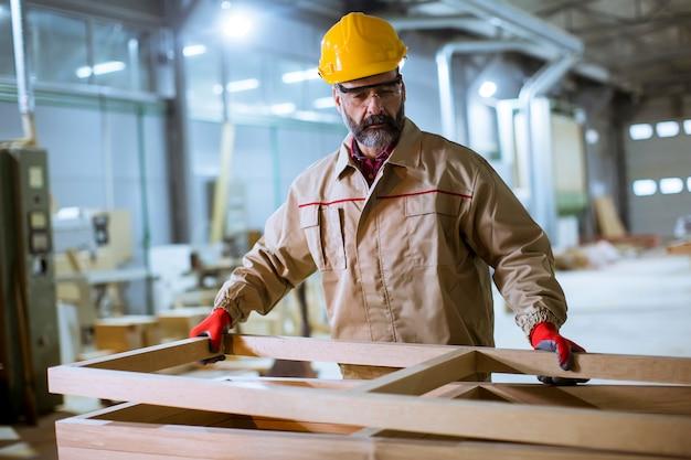 Bonito trabalhador envelhecido médio trabalhando na fábrica de móveis