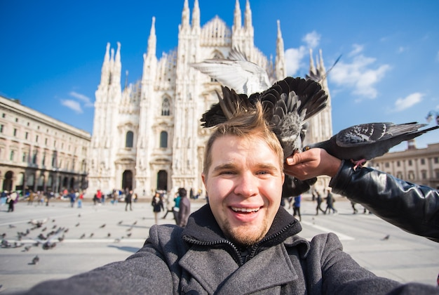 Bonito turista masculino com pombos engraçados fazendo selfie