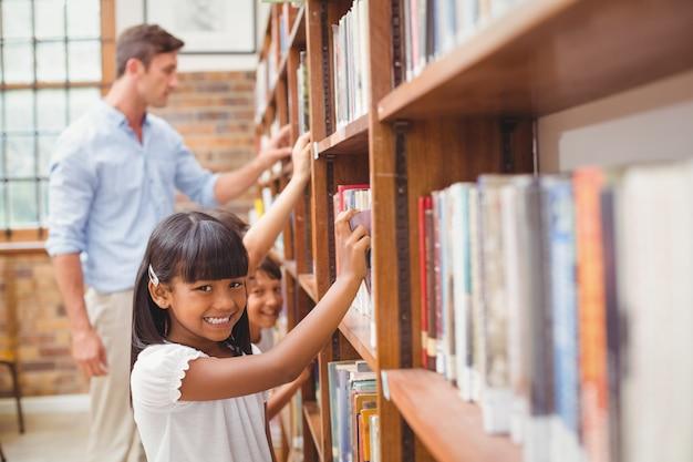Bonitos alunos e professor à procura de livros na biblioteca