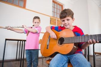 Bonitos alunos tocando flauta e violão em sala de aula