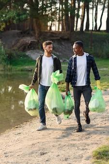 Bonitos amigos ativos de raça mista carregando sacolas plásticas perto do lago depois de limpar o entorno do território do lixo.