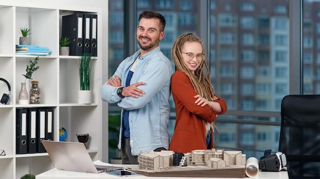Bonitos colegas arquitetos profissionais sorridentes ficam de costas um para o outro no estúdio de design moderno