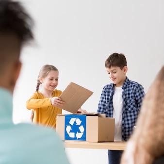 Bonitos crianças aprendendo a reciclar