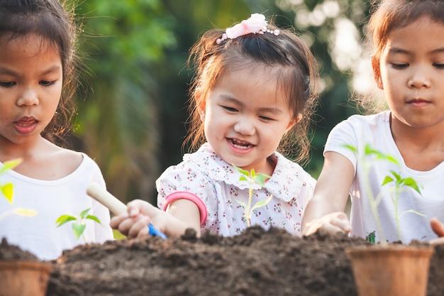 Bonitos crianças asiáticas plantando árvore jovem no solo preto juntos no jardim com diversão