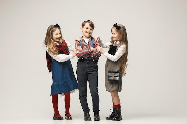 Bonitos crianças elegantes na parede branca
