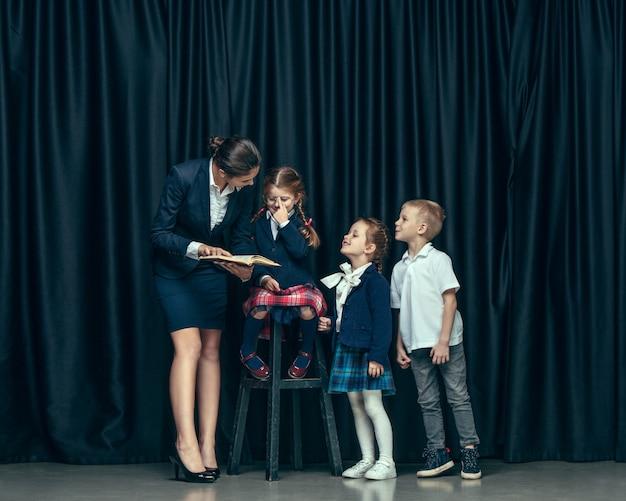 Bonitos crianças elegantes no estúdio escuro. as belas meninas adolescentes e menino juntos