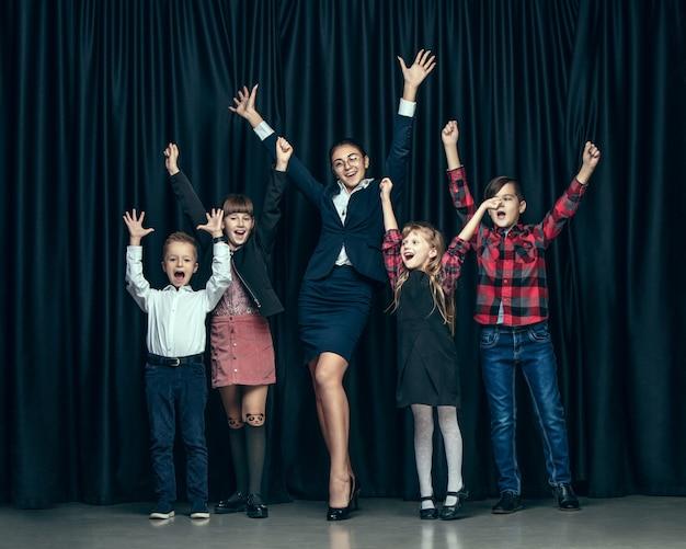 Bonitos crianças elegantes no estúdio escuro. as lindas meninas adolescentes e menino juntos