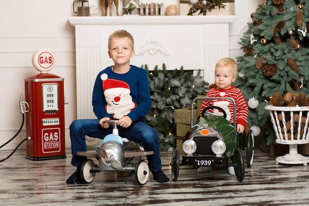 Bonitos dois irmãozinhos estão brincando com carros de brinquedo.