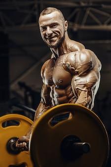 Bonitos homens fortes e atléticos bombeando os músculos do bíceps, exercícios, fitness e conceito de musculação