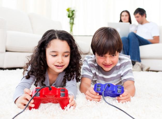Bonitos irmãos jogando videogames deitados no chão