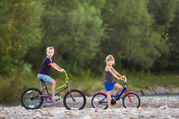 Bonitos jovens crianças loiras, menino e menina, andar de bicicleta de criança na margem do rio de seixos
