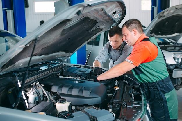 Bonitos mecânicos de uniforme estão trabalhando no serviço automotivo